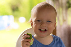 Niño infantil adorable con un pepino en su mano que ríe y que mira la cámara Imagen de archivo
