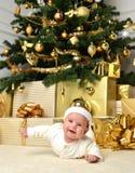Niño infantil del bebé que miente debajo del árbol de navidad con deco de la bola del oro Imagen de archivo