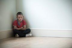 Niño infeliz que se sienta en la esquina del sitio imagenes de archivo