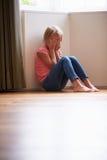 Niño infeliz que se sienta en piso en esquina en casa fotografía de archivo