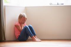 Niño infeliz que se sienta en piso en esquina en casa Fotografía de archivo libre de regalías