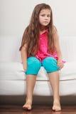 Niño infeliz triste de la niña que se sienta en el sofá Fotos de archivo