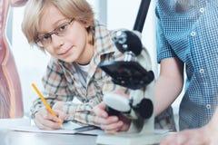 Niño inteligente analítico que anota datos obtenidos Fotografía de archivo libre de regalías