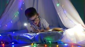 Niño inteligente en el libro de lectura de las lentes en la iluminación de la linterna que miente en tienda con las luces brillan almacen de metraje de vídeo