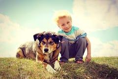 Niño joven afuera con su perro, estilo del vintage Foto de archivo libre de regalías