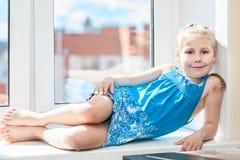 Niño joven alegre que pone en travesaño de la ventana Foto de archivo libre de regalías