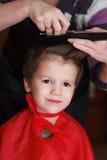 Niño joven con sonrisa en el peluquero que tiene un corte de pelo foto de archivo