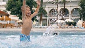 Niño joven del niño del muchacho que salpica en la piscina que tiene pasatiempo de la diversión almacen de metraje de vídeo