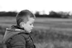 Niño joven deprimido afuera en campo Imagen de archivo libre de regalías