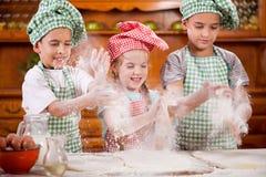 Niño joven divertido tres que sacude las manos con la harina en la cocina Fotografía de archivo
