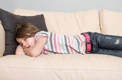 Niño joven dormido en un sofá de cuero Fotografía de archivo libre de regalías