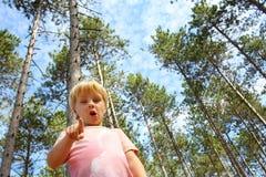 Niño joven en Forest Pointing en la cámara Imagenes de archivo
