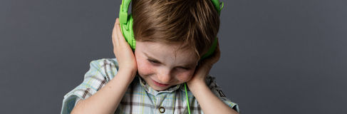 Niño joven enfocado feliz que sostiene los auriculares para escuchar la música Imagen de archivo libre de regalías