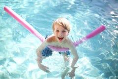 Niño joven feliz que flota en piscina fotografía de archivo