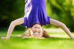 Niño joven feliz que juega de cabeza en hierba verde en parque de la primavera imagen de archivo