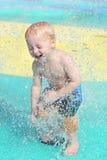 Niño joven feliz que juega en piscina del chapoteo del niño Fotografía de archivo libre de regalías