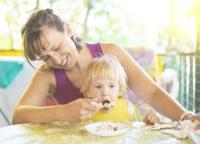 Niño joven lindo de la alimentación de la mamá fotografía de archivo