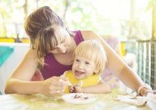 Niño joven lindo de la alimentación de la mamá imagen de archivo