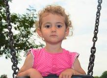 Niño joven, muchacha, jugando en un oscilación en el patio. Imagen de archivo