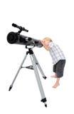 Niño joven o muchacho que mira a través de un telescopio Foto de archivo libre de regalías