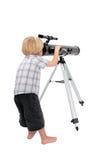 Niño joven o muchacho que mira a través de un telescopio Fotos de archivo