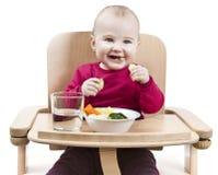 Niño joven que come en alta silla imágenes de archivo libres de regalías