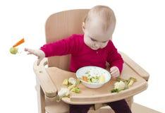 Niño joven que come en alta silla Fotos de archivo
