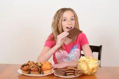 Niño joven que come la barra de chocolate grande foto de archivo