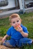 Niño joven que come la manzana Foto de archivo