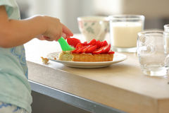 Niño joven que come la torta con las fresas Foto de archivo libre de regalías