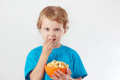 Niño joven que come las palomitas Fotos de archivo