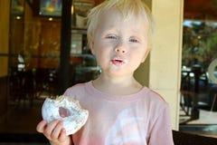 Niño joven que hace la cara divertida mientras que come un buñuelo imagen de archivo