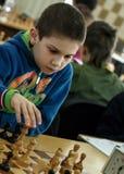 Niño joven que hace un movimiento con un caballo durante un torneo del ajedrez en una escuela, con varios otros competidores en e Fotos de archivo libres de regalías