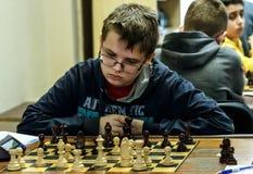 Niño joven que hace un movimiento con un caballo durante un torneo del ajedrez en una escuela, con varios otros competidores en e Fotografía de archivo libre de regalías