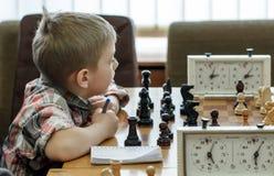 Niño joven que hace un movimiento con un caballo durante un torneo del ajedrez en una escuela, con varios otros competidores en e Imagen de archivo libre de regalías