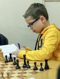 Niño joven que hace un movimiento con un caballo durante un torneo del ajedrez en una escuela, con varios otros competidores en e Fotos de archivo