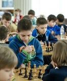 Niño joven que hace un movimiento con un caballo durante un torneo del ajedrez en una escuela, con varios otros competidores en e Foto de archivo libre de regalías
