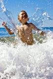 Niño joven que juega en el mar foto de archivo