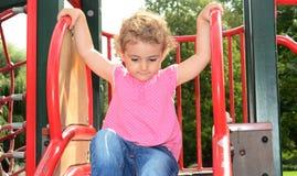 Niño joven que juega en una diapositiva en el patio. Fotos de archivo libres de regalías