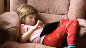 Niño joven que juega en una tableta o un ordenador almacen de metraje de vídeo