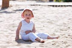 Niño joven que se sienta en la playa con el sombrero rosado Imágenes de archivo libres de regalías