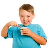 Niño joven sonriente feliz que come el yogur Foto de archivo