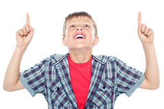 Niño joven sonriente que mira para arriba y el señalar foto de archivo