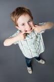Niño joven sonriente que se coloca con la boca grande para la mala conducta cómica Imagen de archivo