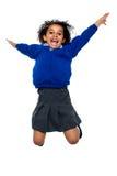 Niño jubiloso de la escuela que salta arriba para arriba en el aire foto de archivo libre de regalías