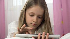 niño 4K que juega la tableta en el dormitorio, muchacha que se relaja en cama, niño usando juegos de la PC almacen de metraje de vídeo