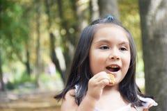 Niño latino que come la galleta Imagen de archivo libre de regalías