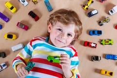 Niño lindo adorable con la porción de diversos coches coloridos del juguete Foto de archivo libre de regalías