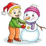 Niño lindo con el muñeco de nieve Fotos de archivo libres de regalías