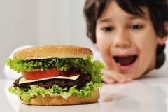 Niño lindo con la hamburguesa Imagen de archivo libre de regalías